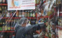 Vendedora atiende desde atrás de la protección de plástico en el mercado Surquillo de Lima. Foto OIT/Cordova
