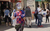 Joven migrante venezolano vende protecciones contra la COVID-19 en las afueras del mercado de Surquillo en Lima. Foto OIT/Cordova