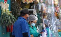 Vendedores de un mercado de Lima frente a sus puestos recubiertos de plástico. Foto OIT/Cordova